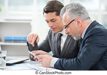 Two businessmen working with documents and tablet computer. Office interior with big window
