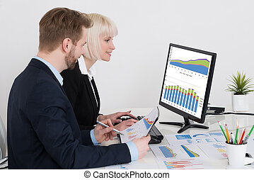 Businesspeople Analyzing Graph On Computer
