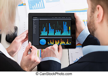Two Businesspeople Analyzing Graph On Digital Tablet