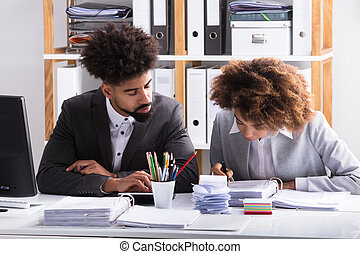 Two Businesspeople Checking Invoice