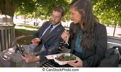 Two businesspeople eating healthy food watching a digital tablet together