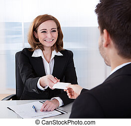 Two happy businesspeople exchanging visiting card in office