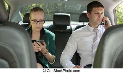 Two businesspeople in backseat of car using phones