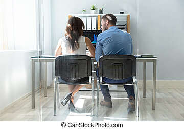 Two Businesspeople Looking At Computer Having Conversation