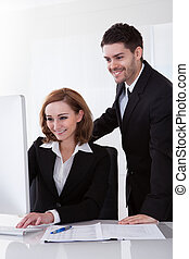 Two businesspeople looking at computer