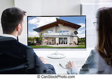 Two Businesspeople Looking At House