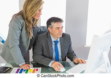 Two businesspeople looking at something on computer