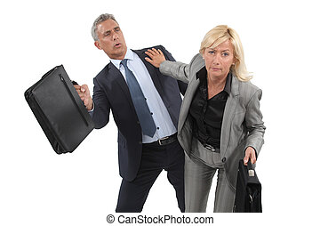 Two businesspeople pushing past each other