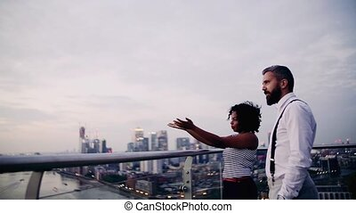 Two businesspeople standing against London view panorama at...