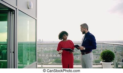 Two businesspeople standing against London view panorama, talking.