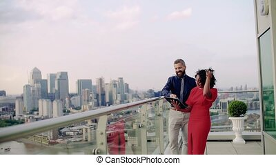 Two businesspeople standing against London view panorama,...