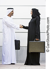 Two businesspeople standing outdoors with briefcases shaking...