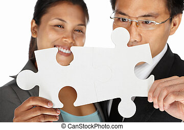 Two businesspeople sucessfuly connect the puzzle