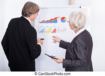 Two Businesspeople With Calculator And Flipchart - Mature...