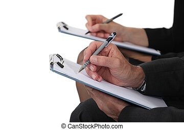 Two businesspeople with clipboards