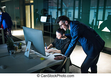 Two businesspeople with computer at desk in an office, working.