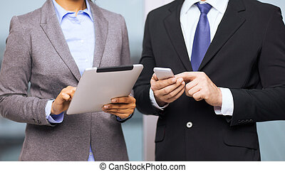 two businesspeople with smartphone and tablet pc - business,...