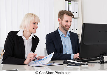 Two Businesspeople Working On Computer