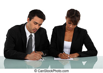 Two businesspeople writing notes