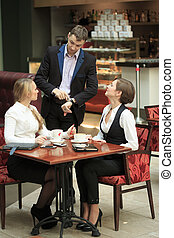 Two businesswoman in a cafe. man looking at the girls -...