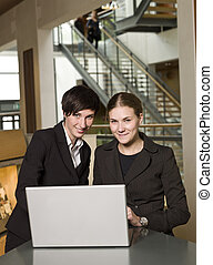 Two businesswoman in front of a computer facing the camera