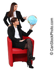 Two businesswoman looking at a globe