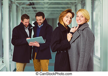 Two businesswoman looking on you in lobby with colleagues at background