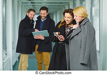 Two businesswoman looking smart phone in lobby with colleagues at background