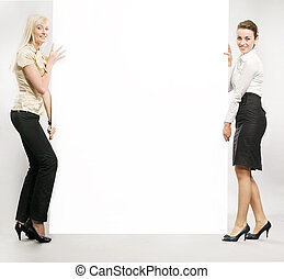 Two businesswomen carrying a white board