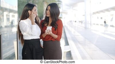 Two businesswomen checking a phone message - Two...