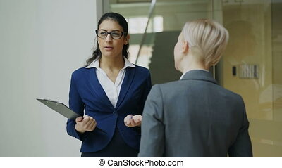 Two businesswomen colleagues talking in modern office...