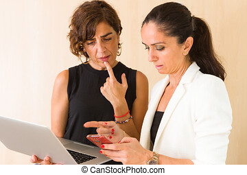 Two businesswomen comparing digital publications between an smart-phone and a laptop