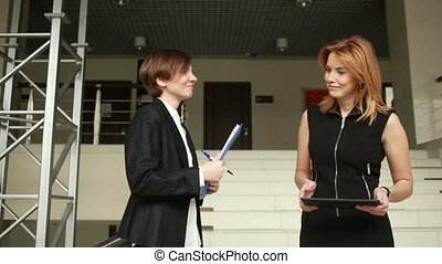 Two businesswomen discussing a contract. go around the office