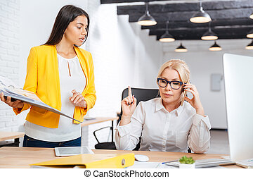 Two businesswomen discussing ideas at the table in the office