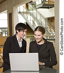 Two businesswomen in front of a laptop