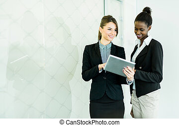 Two businesswomen looking at a tablet with a glass reflection