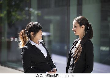 Two Businesswomen outdoors talking.