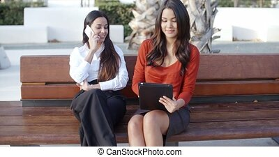 Two businesswomen relaxing in an urban park