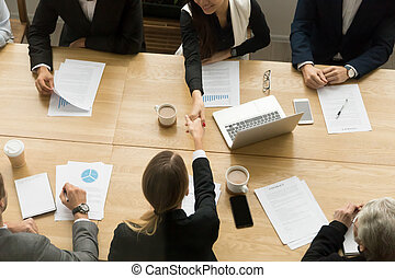 Two businesswomen shaking hands at group meeting, top view