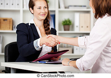 Two businesswomen shaking hands on a deal