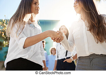 Two businesswomen shaking their hands outside