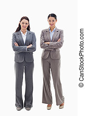 Two businesswomen smiling and crossing their arms