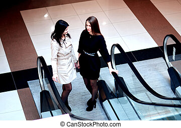 two businesswomen talking, standing on the escalator in the business center