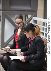 Two businesswomen with digital tablet in a modern urban setting.