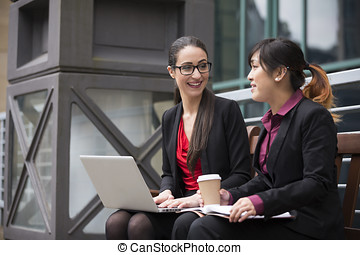 Two businesswomen with laptop in a modern urban setting.