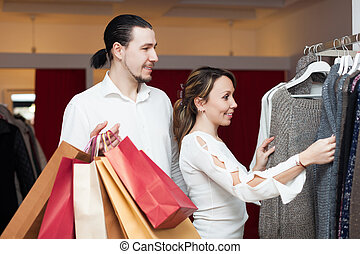 Two buyers with shopping bags  at clothing shop