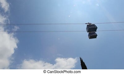 two cabins moving on funicular against sky with sun above...