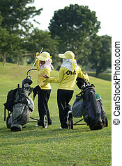 Two caddies at a golf course in Thailand