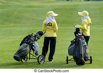 Two caddies, waiting on the fairway at a golf course in Thailand.