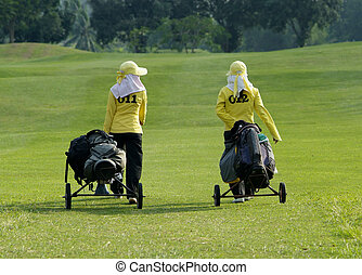 Two caddies walking down the fairway of a golf course in Thailand